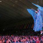 chica con alas colgada frente al público